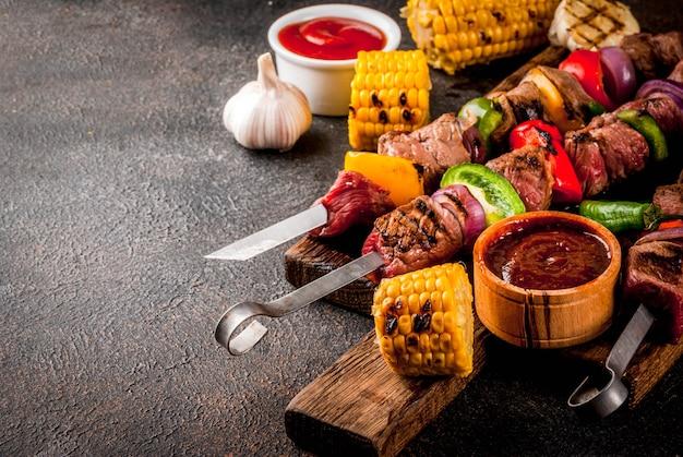 Fresco, cucinato in casa alla brace, carne di manzo shish kebab con verdure e spezie, con salsa barbecue e ketchup,