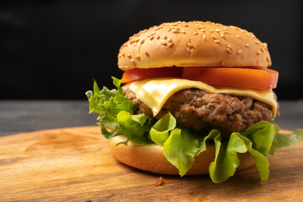 Fresco gustoso hamburger fatti in casa con verdure fresche e formaggio su un tagliere.