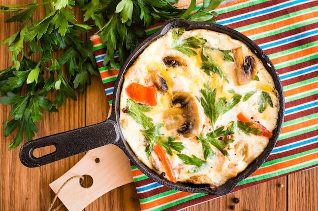 Frittata a base di uova, pomodori, funghi, pollo e formaggio in una padella e prezzemolo fresco su un tavolo di legno. vista dall'alto