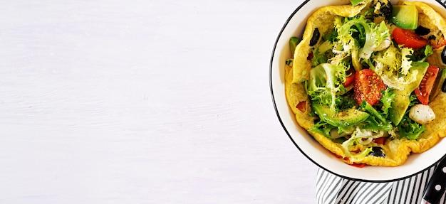 Frittata con pomodori freschi, olive nere, avocado e mozzarella.
