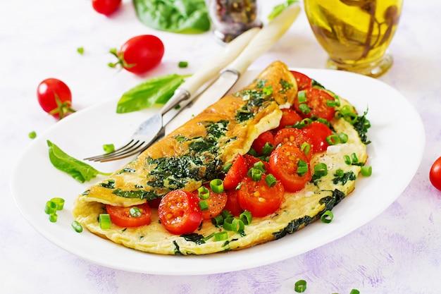 Frittata con pomodori, spinaci e cipolla verde sul piatto bianco.