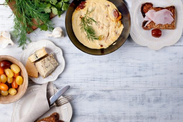 Frittata con pomodoro in padella per colazione, formaggio e verdure su un fondo di legno bianco