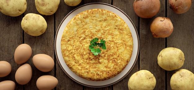 Frittata di patate sul tavolo nel campo, con gli ingredienti necessari