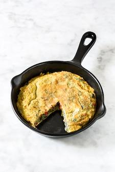 Frittata fatta di uova e verdure in una padella di ferro su marmo bianco