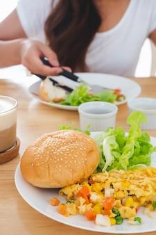 Frittate per la colazione, pane, hamburger e verdure su un piatto bianco, mangiati sul retro sfocato
