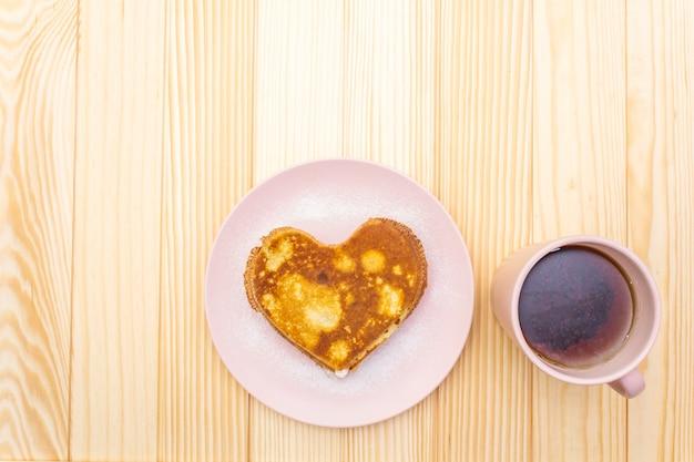 Frittelle a forma di cuore per colazione romantica con marmellata di fragole e tè nero
