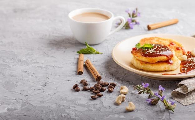 Frittelle al formaggio con salsa al caramello su un piatto in ceramica beige e una tazza di caffè sul cemento grigio