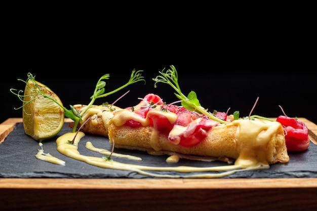 Frittelle al salmone, su una pietra nera, ardesia, su una tavola di legno