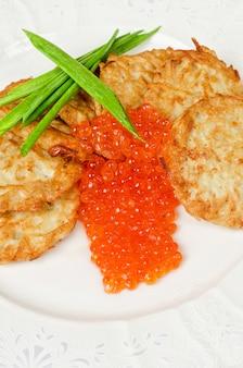 Frittelle con caviale rosso e cipolla verde piatto closeup