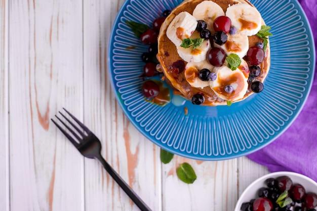 Frittelle deliziose e rigogliose con frutta e bacche fresche, versate con caramello salato. menta, tè, succo d'arancia, latte sul tavolo.