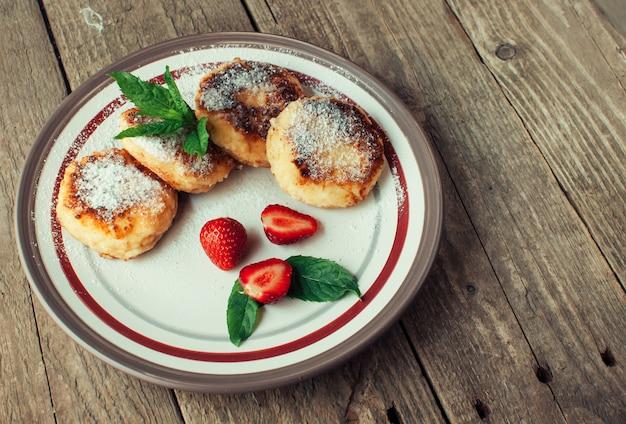 Frittelle di cagliata con fragole e menta e zucchero a velo in un piatto bianco.