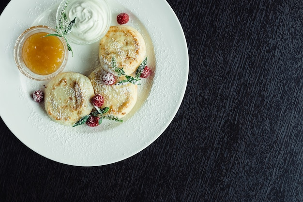 Frittelle di formaggio con lamponi e miele su un piatto bianco su un tavolo di legno
