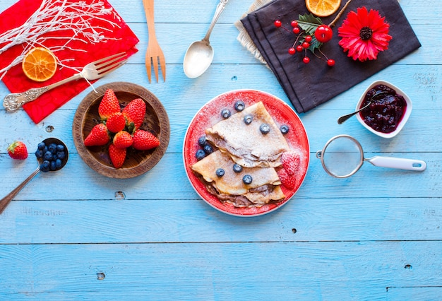 Frittelle di fragole fresche o crepes con bacche e cioccolato