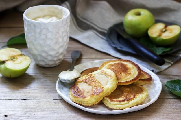 Frittelle di mele fatte in casa con panna acida, caffè e mele verdi su un legno