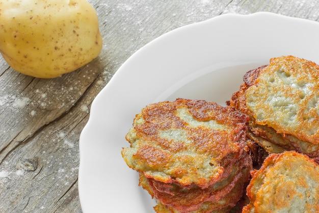 Frittelle di patate con una crosta dorata in un piatto di ceramica bianca e una patata cruda