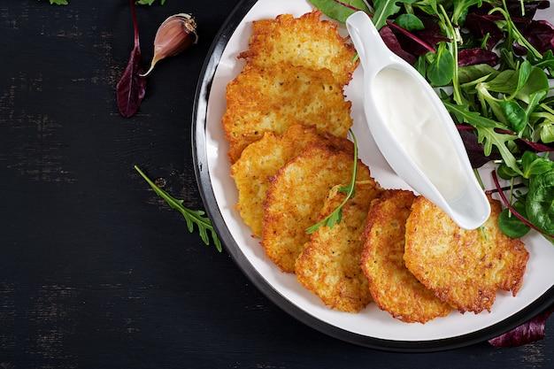 Frittelle di patate / draniki / pancakes serviti con panna acida.