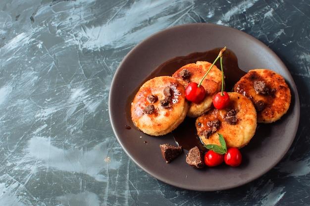 Frittelle di ricotta cheesecakes con ciliegie e cioccolato su uno sfondo nero tavolo in cemento.