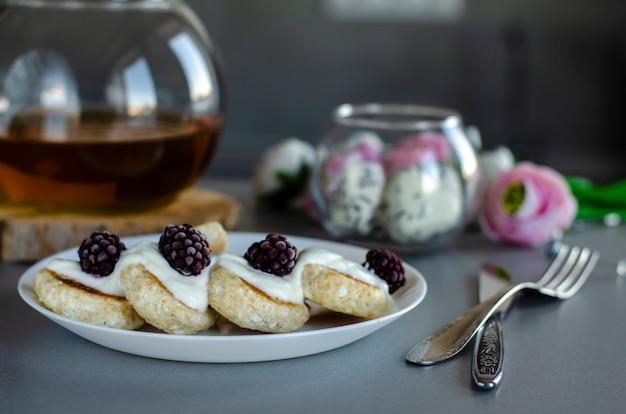 Frittelle di ricotta con more e panna acida per una sana colazione.