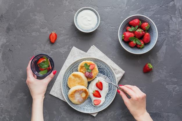 Frittelle di ricotta con panna acida e fragole per colazione o pranzo su grigio.
