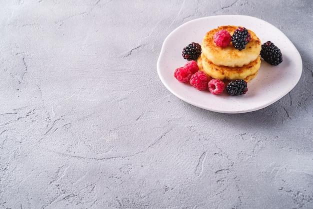 Frittelle di ricotta, frittelle di cagliata dessert con lampone e bacche di mora in lamiera su sfondo di pietra di cemento, angolo di copia spazio