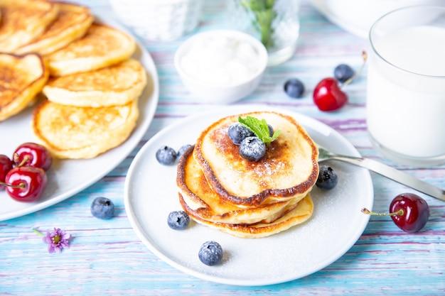 Frittelle di ricotta (syrniki). cheesecakes fatti in casa da ricotta con panna acida, frutti di bosco e latte. piatto tradizionale russo. avvicinamento.