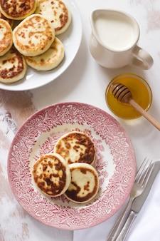 Frittelle di ricotta, syrniki fatti in casa con miele e panna acida.
