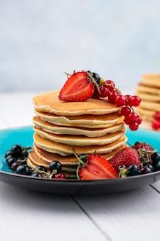 Frittelle di vista frontale con fragole ribes nero e rosso su un piatto