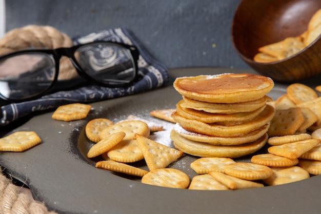 Frittelle di vista frontale e biscotti con occhiali da sole su grigio