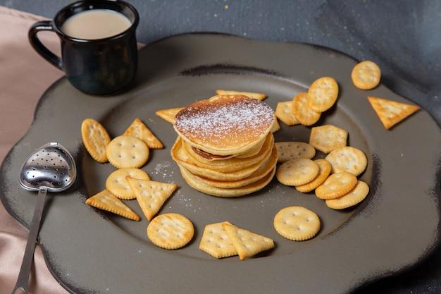 Frittelle di vista frontale e patatine con tazza di latte nera su grigio
