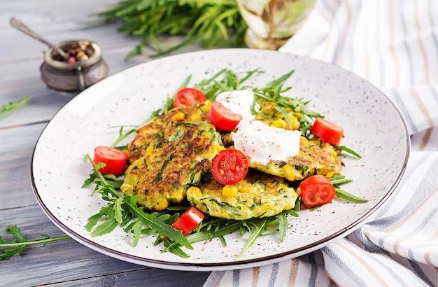 Frittelle di zucchine con mais e panna acida servite rucola, insalata di pomodori.