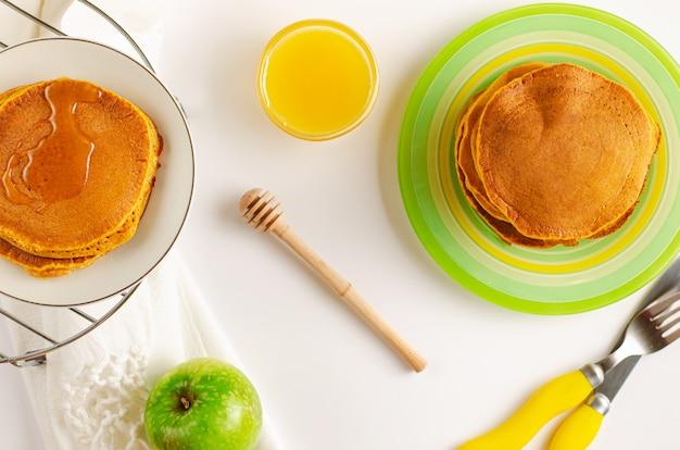 Frittelle discrete con miele su sfondo bianco