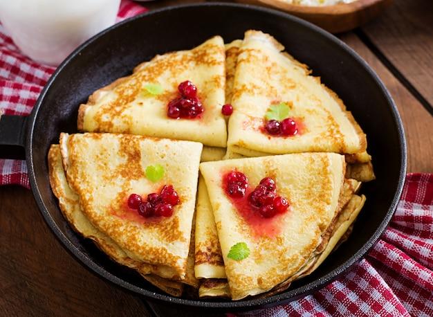 Frittelle dorate con marmellata di mirtilli rossi e miele in stile rustico. vista dall'alto