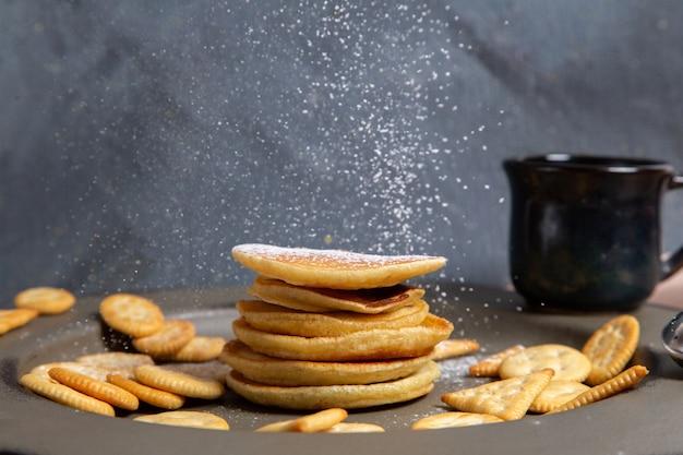 Frittelle e cracker di vista frontale con tazza di latte nera su gray