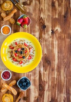 Frittelle fatte in casa con frutti di bosco freschi, fragole, mirtilli e sciroppo d'acero su un fondo di legno.