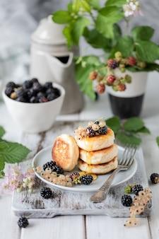Frittelle fatte in casa con frutti di bosco, le more, il miele sul piatto, un ramo di una sveglia blackberry su fondo di legno bianco