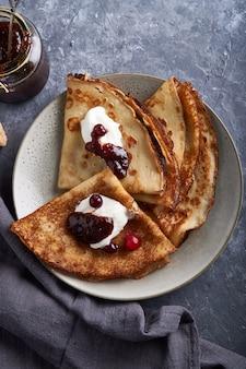 Frittelle fatte in casa tradizionali con mirtilli rossi e panna acida servita sul tavolo di pietra grigia. vista dall'alto.