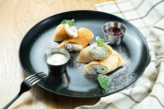Frittelle sottili fatte in casa o crepes con ricotta su un piatto nero. cucina francese. messa a fuoco selettiva. servizio al ristorante.