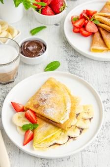 Frittelle sottili o crepes con crema al cioccolato, banana e fragole su un piatto bianco con un bicchiere di cappuccino su uno sfondo di legno chiaro. orientamento verticale. copia spazio.