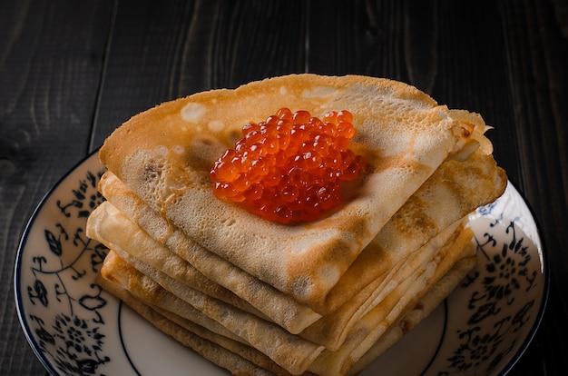 Frittelle sottili piatto tradizionale festivo con caviale rosso.