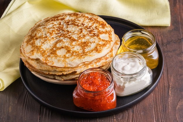 Frittelle su un piatto nero. ripieni: panna acida, caviale rosso, miele. giorno del pancake. tradizione russa nell'ultima settimana prima di pasqua, ci sono frittelle con diversi ripieni.