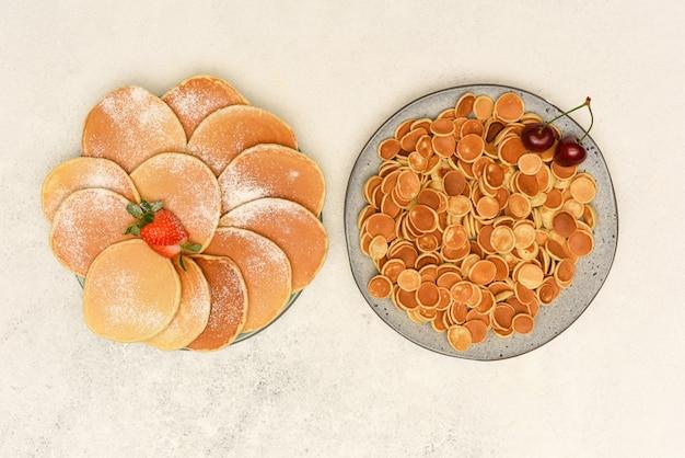 Frittelle tradizionali e frittelle di cereali in lastre grigie su sfondo chiaro. frittelle di vista dall'alto con frutti di bosco.