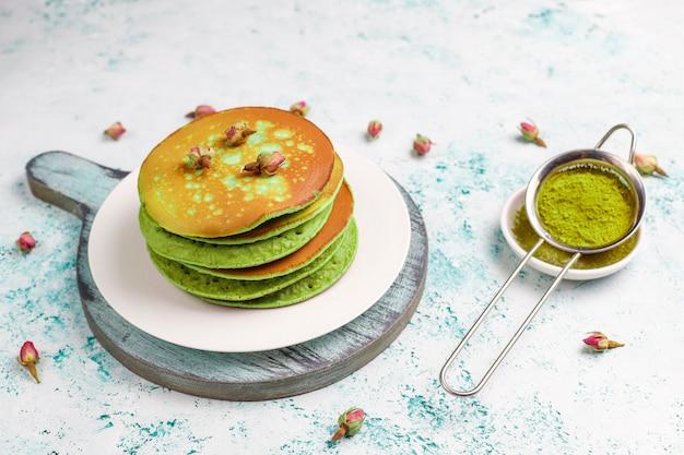 Frittelle verdi con matcha in polvere con marmellata rossa sul tavolo luminoso