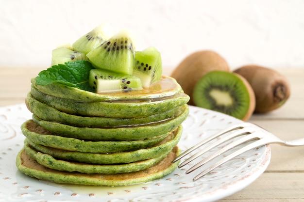 Frittelle verdi con miele e kiwi. su uno sfondo chiaro.