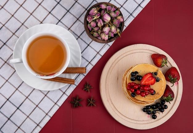 Frittelle vista dall'alto con ribes rosso e nero e fragole su un vassoio con una tazza di tè e cannella su uno sfondo rosso