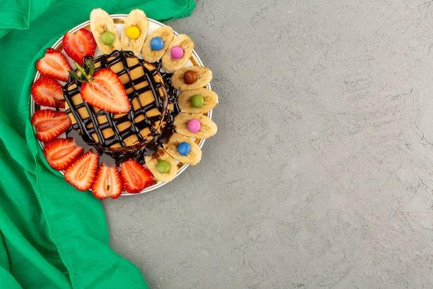 Frittelle vista dall'alto insieme a fragole e banane a fette di cioccolato versato sulla luce