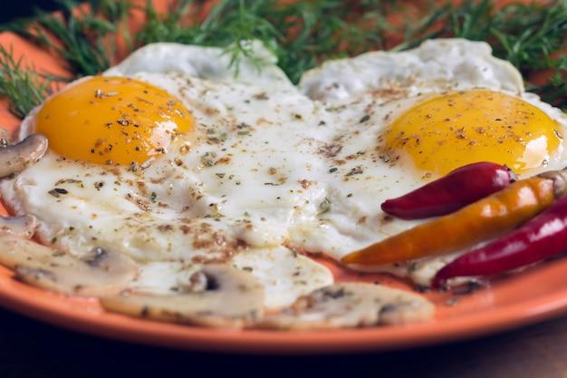 Fritto due uova con champignon, aneto e peperoncino rosso