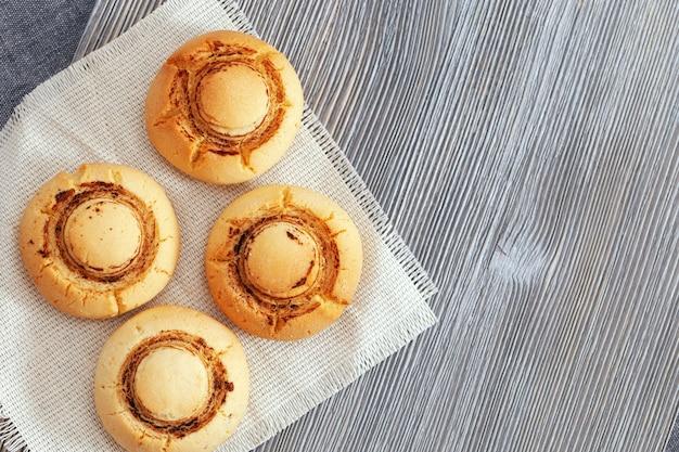 Frollini a forma di funghi. biscotti al forno sulla tavola di legno. dessert dell'alimento con lo spazio della copia. vista dall'alto.