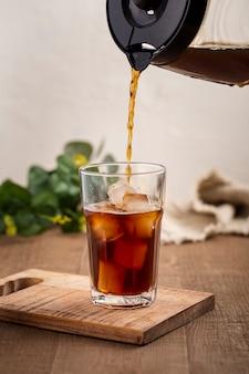 Front vie caffè versato in un bicchiere alto