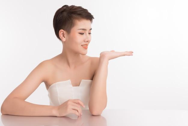 Fronte asiatico della giovane donna del primo piano con pelle pulita.