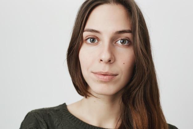 Fronte attraente della giovane donna del primo piano che osserva macchina fotografica